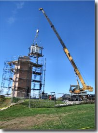 A telescopic crane establishes  the new lantern atop the lighthouse (Photo by Ann-Marie Trapani)