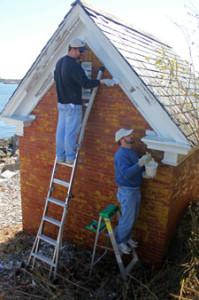 Volunteers work on the oil house