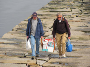 Craig Mathieson and Brian Trask carry supplies and the light's cash register out the breakwater (Photo by Bob Trapani, Jr.)