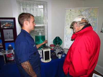FN Alex Lozanski talks with a visitor about light emitting diode (LED) beacons and their role on buoys and in lighthouses today. (Photo by Bob Trapani, Jr.)