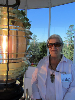 Marla Rogers with Owls Head Light's fourth order Fresnel lens (Photo by Bob Trapani, Jr.)