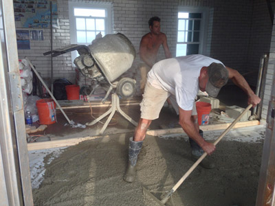 Alan Spier (foreground) and Dave Eastman work on pouring cement for a new engine room floor at Rockland Breakwater Light (Photo by Bob Trapaani, Jr.)