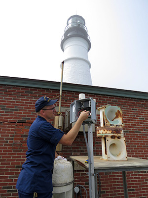 EM1 Tony Robb inspects the MRASS system at Portland Head Light. (Photo by Bob Trapani, Jr.)