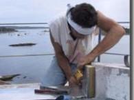 Joseph Gnazzo Co. worker installs flashing on Avery Point Light